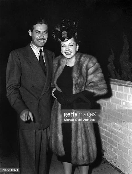 Actress Anne Baxter with husband actor John Hodiak pose on a street in Los Angeles California