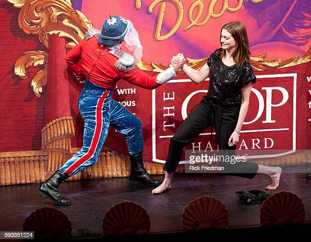 Actress Anne Hathaway arm wrestles cast member Mike Blumenthal during a skit while being honored as Harvard's Hasty Pudding Theatricals Woman of the...