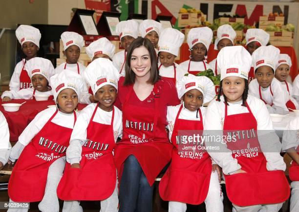 Actress Anne Hathaway poses with local new york school children during an appearance at the Kids Cafe in Harlem for the Netflix Holiday Gift Program...