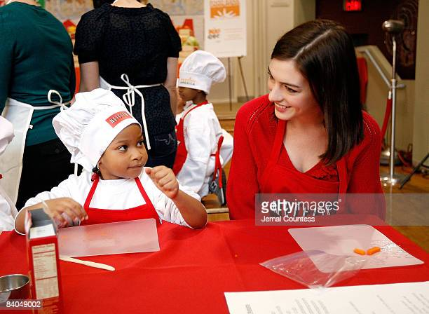 Actress Anne Hathaway sits with Niya McDowell of New York City during an appearance at the Kids Cafe in Harlem for the Netflix Holiday Gift Program...