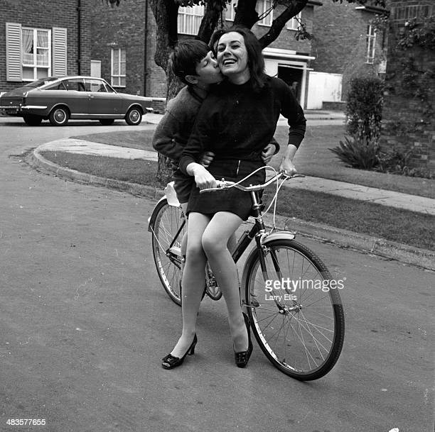 Actress Anne Rogers posing on a bicycle with her son Timothy Hall London 22nd May 1968