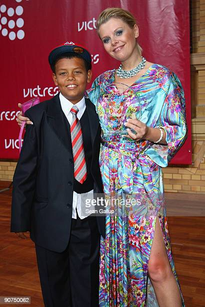 Actress AnneSophie Briest holds her Victress Award with her son Jahmar Walker at the Victress Day Gala 2009 on September 14 2009 in Berlin Germany