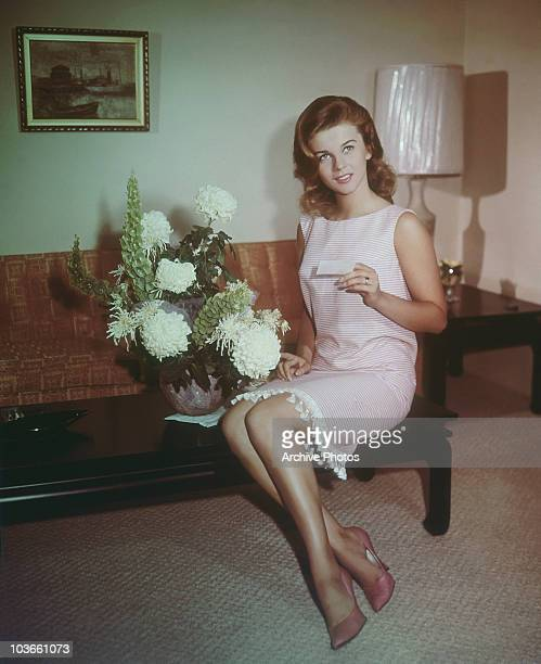 Actress AnnMargret pictured sitting on a coffee table wearing a pink and white dress alongside a vase of flowers USA circa 1965