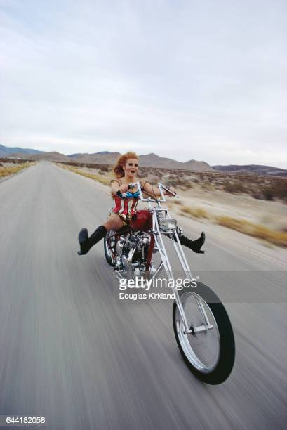 Actress AnnMargret rides a chopper motorcycle in the desert outside Las Vegas She wears a shiny starspangled banner bodysuit | Location Near Las...
