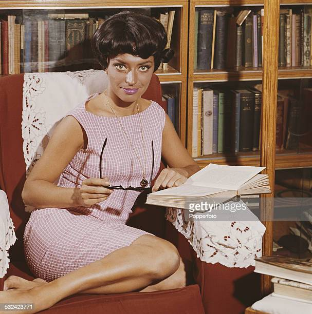 Actress April Olrich posed wearing a pink sleeveless summer dress whilst sitting in a chair in a library reading a book in 1963