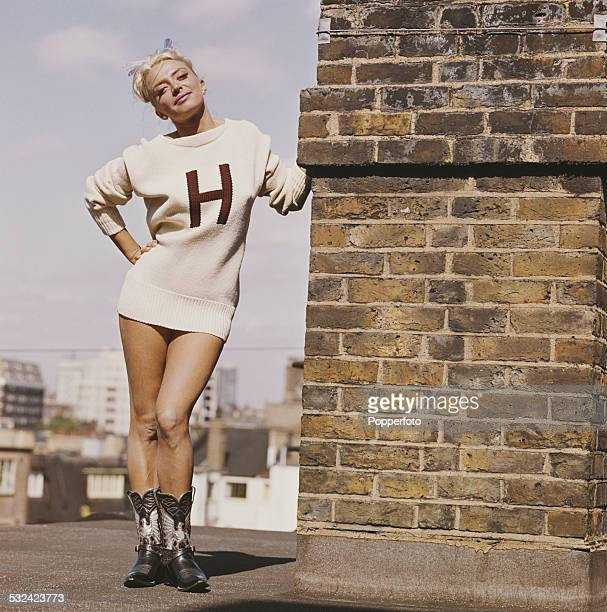 Actress April Olrich posed wearing a white knit sweater bare legs and comboy boots on a rooftop in London in 1963