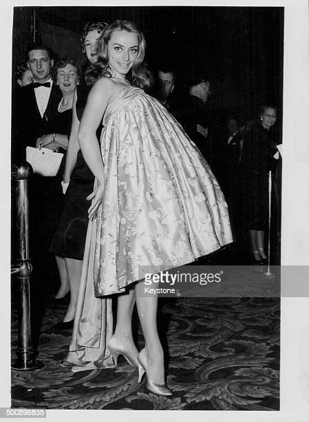 Actress April Olrich wearing a dress she made herself from a Chinese tapestry arriving at the premiere of the movie 'No Trees in the Street'...