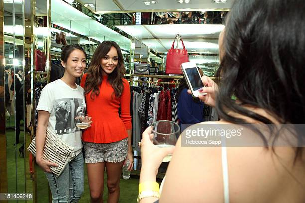 Actress Ashley Madekwe poses for a photo with a fan at Fashion's Night Out At Tory Burch at Tory Burch on September 6 2012 in Los Angeles California