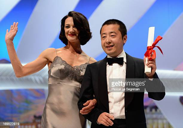 Actress Asia Argento stands next to Jia Zhangke of 'Tian Zhu Ding' as he receives the best screenplay award during the Closing Ceremony during the...