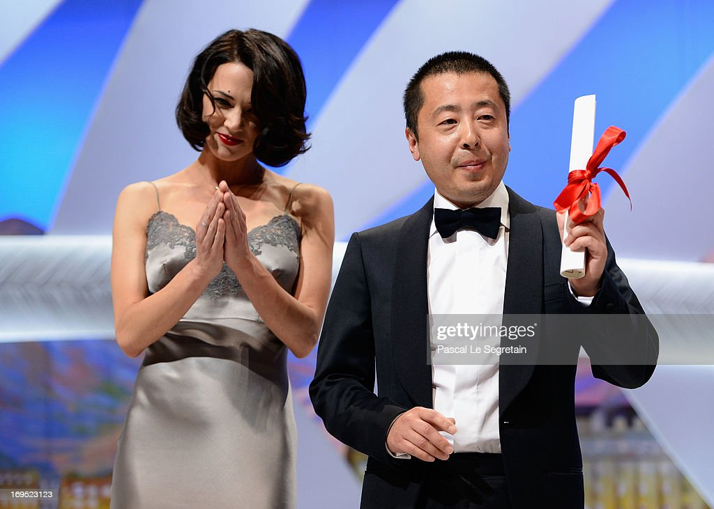 Actress Asia Argento stands next to Jia Zhangke of 'Tian Zhu Ding' ('A Touch of Sin') as he receives the best screenplay award during the Closing Ceremony during the 66th Annual Cannes Film Festival at the Palais des Festivals on May 26, 2013 in Cannes, France.