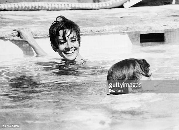 Actress Audrey Hepburn and actor Albert Finney slosh around happily during the filming of a swimming pool sequence here July 8 for their new movie...