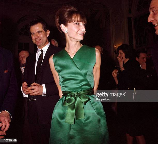 Actress Audrey Hepburn at a reception in a sleeveless emerald green satin Vneck cocktail dress with matching tied belt in London circa 1965