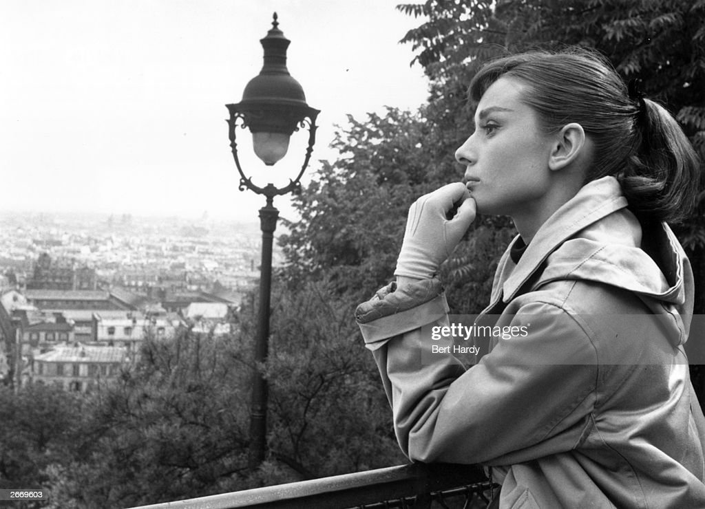 Actress Audrey Hepburn (1929-1993) contemplates Paris where she is filming her first musical, 'Funny Face' with Fred Astaire. Picture Post - 8540 - Audrey Dances With Astaire - pub. 1956