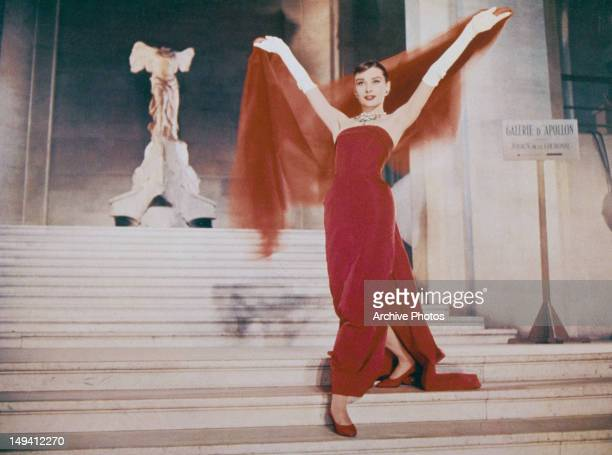 Actress Audrey Hepburn descends the Daru Staircase at the Louvre in Paris in a scene from the film 'Funny Face' 1957 The ancient marble sculpture of...