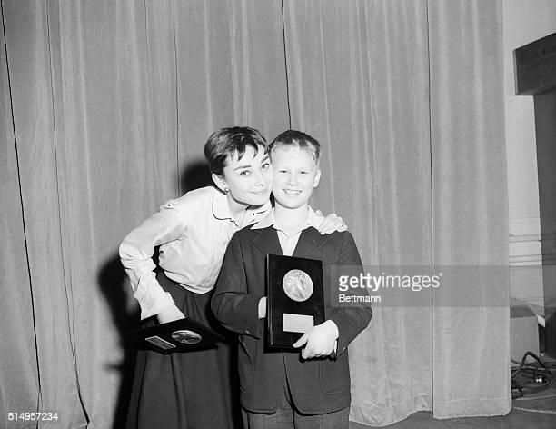 Actress Audrey Hepburn gives fellow Thespian Brandon De Wilde a congratulatory hug as he holds a copy of Look magazine's 13th annual Film achievement...