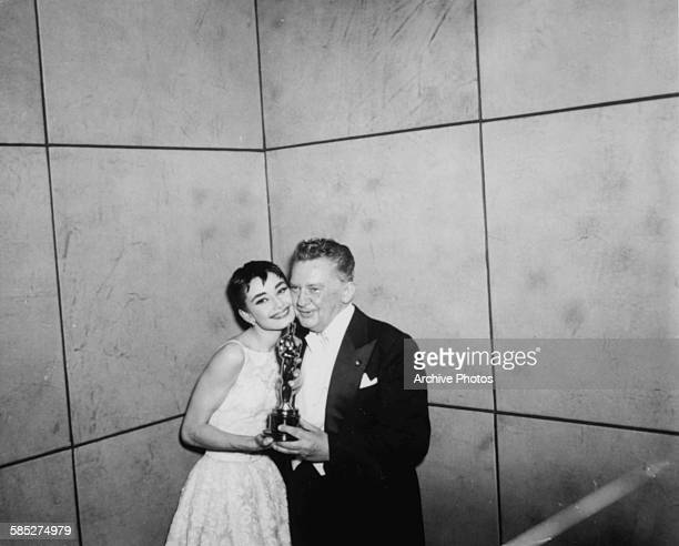 Actress Audrey Hepburn holding her Best Actress Oscar for the film 'Roman Holiday' with actor Jean Hersholt at the 26th Academy Awards New York March...