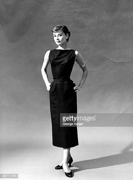 Actress Audrey Hepburn in short hairstyle, elegantly standing in front of seamless w. Hands on hips.