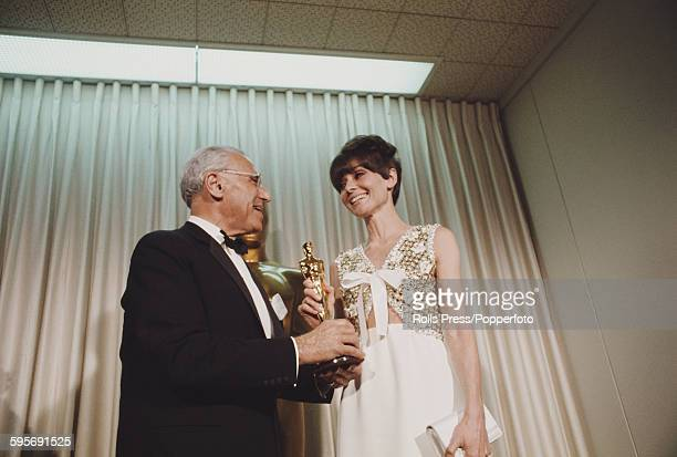 Actress Audrey Hepburn pictured standing with American film director George Cukor at the 40th Academy Awards at the Santa Monica Civic Auditorium in...