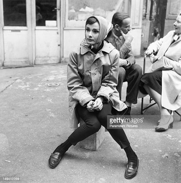 Actress Audrey Hepburn sitting on a crate near the Eiffel Tower in Paris during the filming of 'Funny Face' 1956 Costar Fred Astaire is behind her