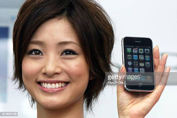 Actress Aya Ueto poses with an Apple iPhone during a ceremony on the first day of its Japanese launch at an electronics store on July 11 2008 in...