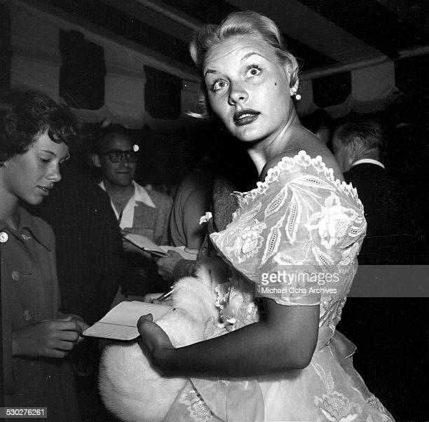 Actress Barbara Payton signs autographs for fans outside Mocambo's in Los AngelesCA