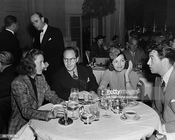 Actress Barbara Stanwyck and her husband actor Robert Taylor have dinner with friends in Los Angeles California