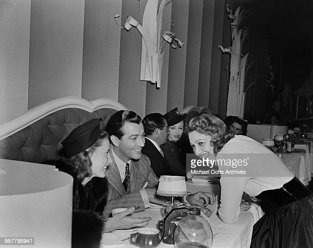 Actress Barbara Stanwyck and her husband actor Robert Taylor talk with actress Mary Livingston in Los Angeles California