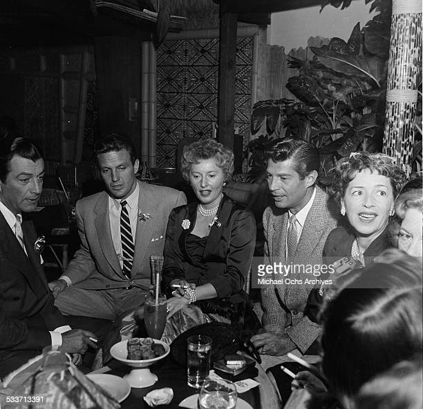 Actress Barbara Stanwyck with husband Robert Taylor and Robert Stack attend a cocktail party for the Hollywood Press Club in Los AngelesCA