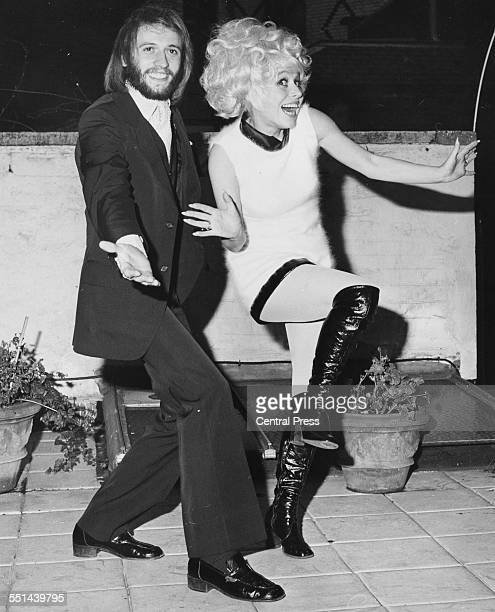 Actress Barbara Windsor and musician Maurice Gibb, of the band 'Bee Gees', joking around at a reception for the musical 'Sing a Rude Song', at the...