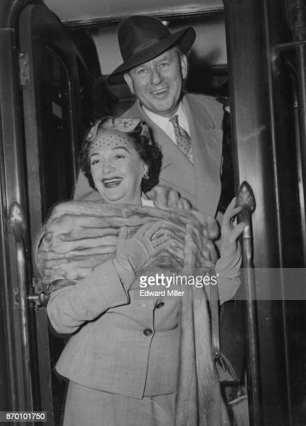Actress Bebe Daniels and her husband actor Ben Lyon arrive at Waterloo Station in London on the 'Queen Mary' boat train from America 12th October 1954