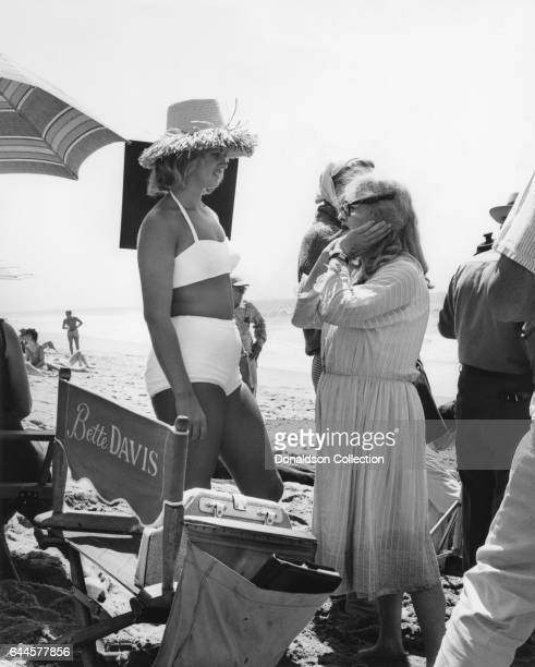 Actress Bette Davis and her daughter Barbara Merrill chat on the beach between takes in a publicity still for the Warner Bros film 'What Ever...