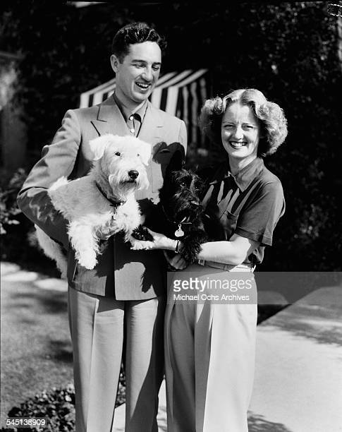 Actress Bette Davis and her husband Harmon Oscar Nelson Jr pose outside with their dog in Los Angeles California
