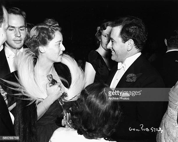 Actress Bette Davis holding her Oscar for the film 'Jezebel' as she talks to director William Wyler at the 11th Academy Awards Los Angeles February...
