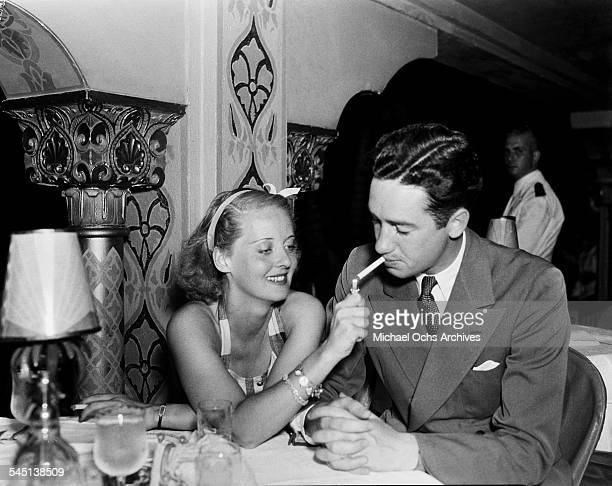 Actress Bette Davis lights a cigarette for husband Harmon Oscar Nelson Jr in Los Angeles California
