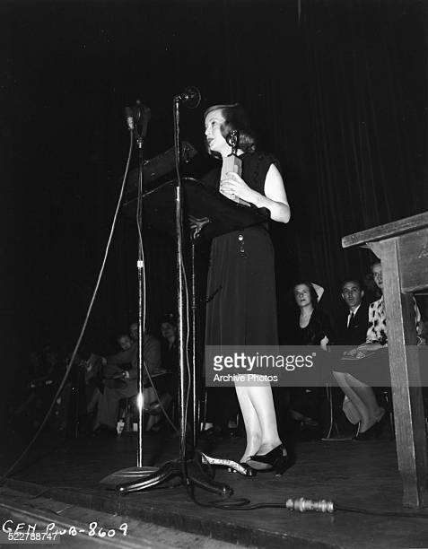Actress Bette Davis on stage holding a trophy at a war bond drive during World War Two circa 1941