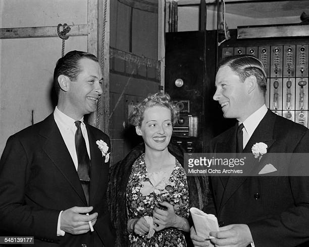 Actress Bette Davis poses with actor Robert Montgomery and George Murphy in Los Angeles California