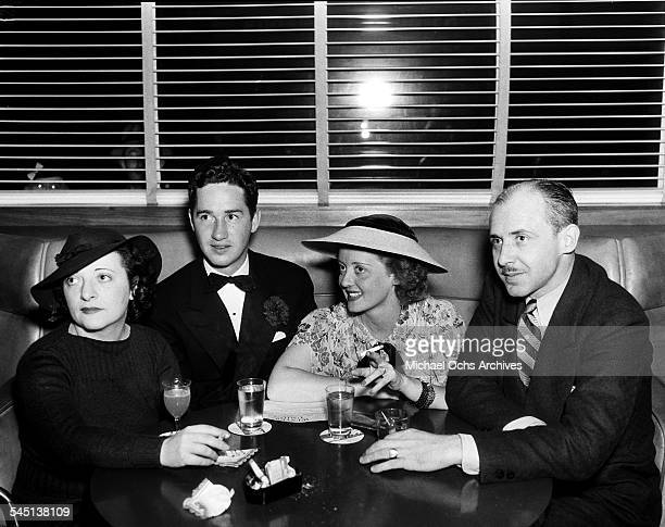 Actress Bette Davis sits with husband Harmon Oscar Nelson Jr and friends at a cafe in Los Angeles California