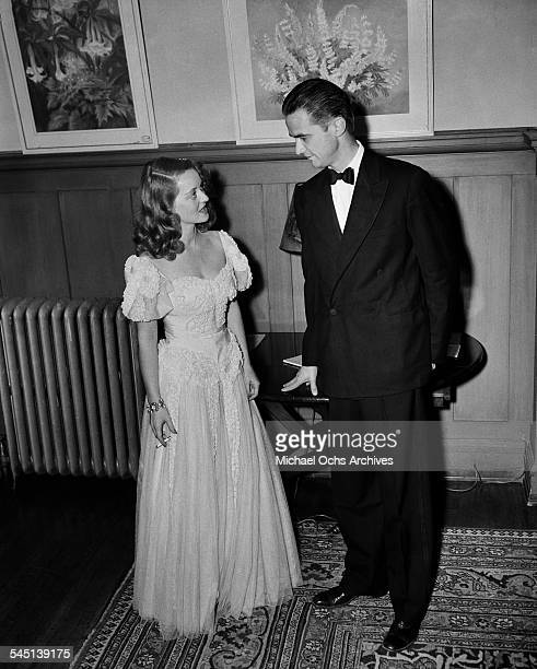 Actress Bette Davis talks with Howard Hughes at an event in Los Angeles, California.
