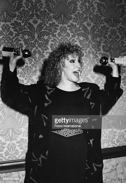 Actress Bette Midler holding her two awards in the air both for the film 'The Rose' at the Golden Globe Awards Los Angeles January 1980