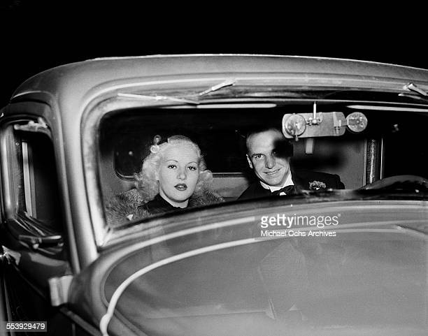 Actress Betty Grable and husband actor Jackie Coogan pose in their car in Los Angeles California