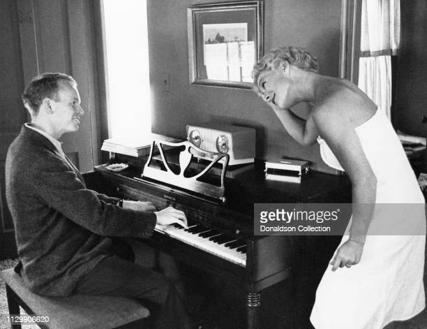 Actress Betty Hutton poses for a portrait with a man playing piano in circa 1958