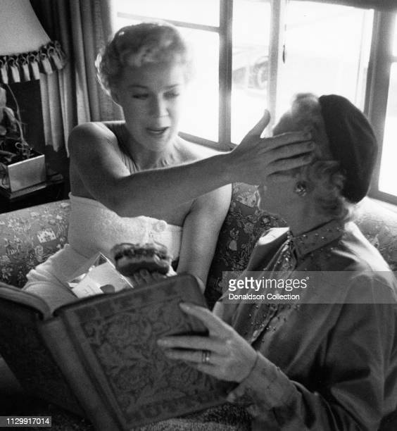 Actress Betty Hutton poses for a portrait with a woman n 1950