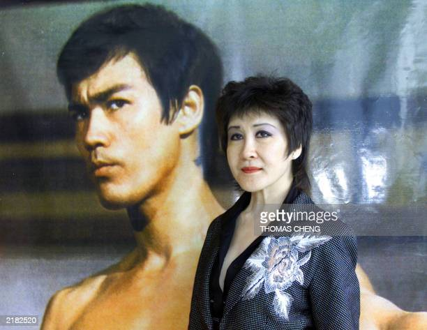 Actress Betty Ting Pei poses next to a Bruce Lee portrait during the exhibition opening ceremony of Bruce Lee's 30 anniversary of his death in Hong...
