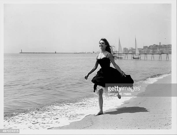 Actress Brigitte Bardot running barefoot along the beach, Cannes, France, April 28th 1956.