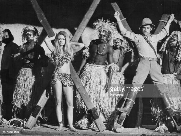 Actress Brigitte Bardot wearing a leopard print costume surrounded by tribesmen in a scene from the movie 'Rum Boulevard' or 'Rum Runners' Almeria...