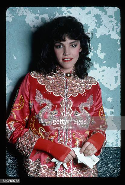 Actress Brooke Adams poses in a red Chinesestyle jacket