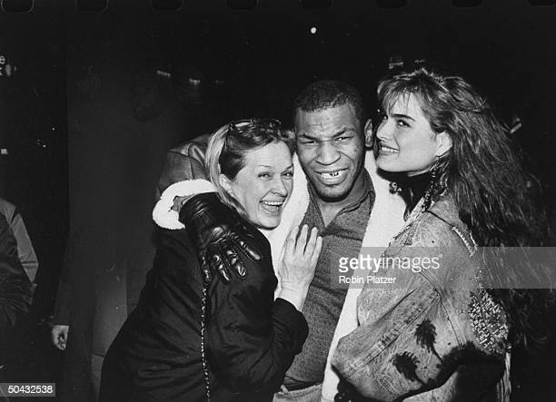 Actress Brooke Shields w mom Teri both getting a hug fr boxer Mike Tyson at the premiere of the film Biloxi Blues
