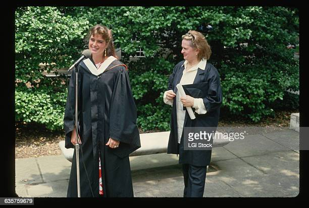 Actress Brooke Shields wears a graduation gown as she speaks into a microphone on her graduation day at Princeton University