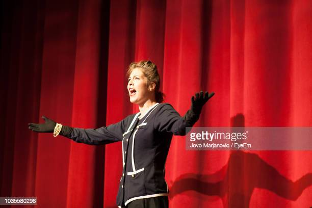 actress by red curtain performing - acting performance stock pictures, royalty-free photos & images