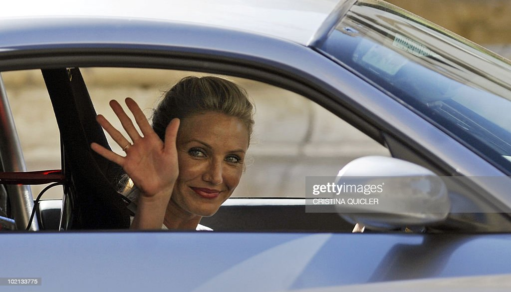 US actress Cameron Diaz waves while driving a car in Sevilla on June 16, 2010, to recreate scenes from the film 'Knight and Day' by US director James Mangold. US actors Tom Cruise and Cameron Diaz are in Sevilla to attend the international premiere of Mangold's new film.
